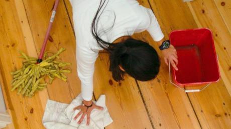 Eine Frau putzt den Fußboden. Foto: Ralf Hirschberger/Illustration