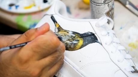 Ein Turnschuh wird in der Manufaktur «Sneaker Surgery» mit einem Bild des neuseeländischen Vogels Hihi (Gelbbandhonigfresser) bemalt. Foto: Daniel Bockwoldt/dpa