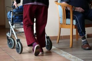 Eine ältere Frau geht mit einem Rollator über einen Flur eines Pflegeheims. Foto: Jens Büttner/zb/dpa