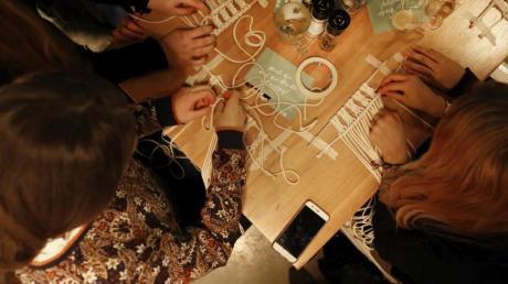 Teilnehmer eines Makramee DIY-Workshop arbeiten zusammen.