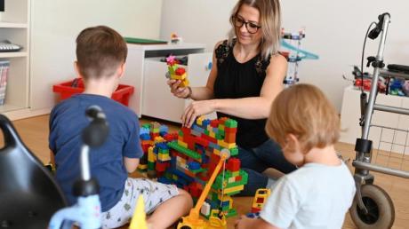 Jule Walter spielt in ihrem Wohnzimmer mit ihren Kindern. Rechts steht ein Rolllator und links ein Kinderdreirad.