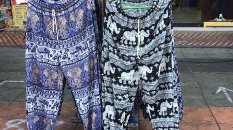 Zwei sogenannte Elefantenhosen hängen an einem Kleiderständer an einer Straße in Thailands Hauptstadt Bangkok.
