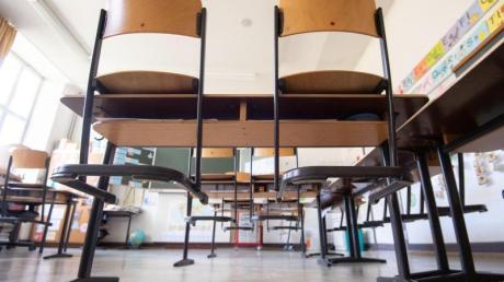 Stühle stehen im Klassenzimmer einer vierten Klasse einer Grundschule nach Schulschluss auf den Tischen.