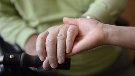 Eine junge Frau hält in einem Seniorenpflegeheim die Hände eines alten Mannes.