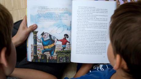 Zwei Kinder lesen das Kinderbuch «Jim Knopf und Lukas der Lokomotivführer» des Autors Michael Ende.