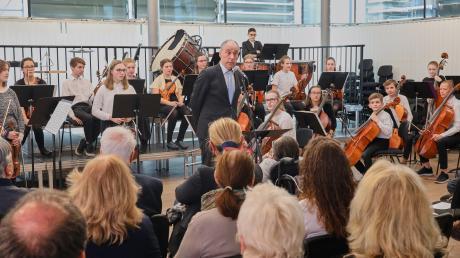 Schulleiter Karl Höldrich bei seiner Begrüßungsrede zur Einweihung der neuen Übungsräume in der Mozartvilla. Im Hintergrund das Schüler- und Jugendorchester der Musikschule Augsburg, das für den musikalischen Rahmen sorgte.