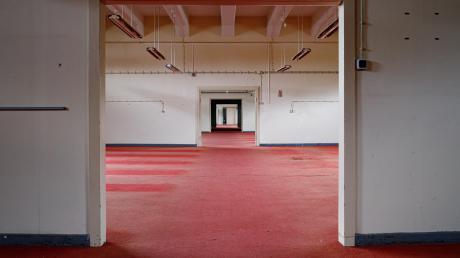 So sieht es im oberen Stockwerk der Halle 116 aus: eine endlose Betonflucht aus Fluren, Türen und wieder Fluren. Auf dem Boden ist roter, teils vergammelter und durchlöcherter Teppich verlegt.