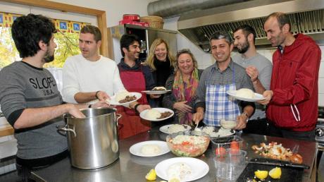 Flüchtlinge, Ehrenamtliche und Ehrenamtskoordinatorin kochen gemeinsam in der Freien Evangelischen Gemeinde in Kriegshaber.