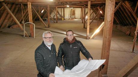Pfarrer Gerhard Groll und Ingenieur Anton Schiele (rechts) erläutern im Dachstuhl der Kirche Heiligste Dreifaltigkeit die bevorstehende Sanierung.