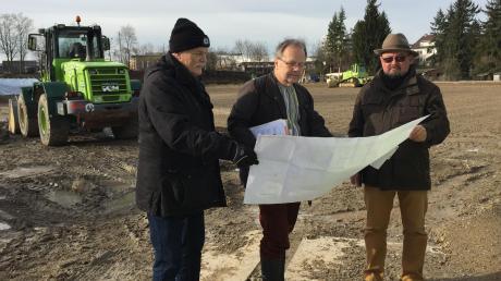 Anton Wolff, Peter Sterz und Stefan Oberschmid (von links) sehen sich die Pläne für den Bau des Hybridrasenplatzes an.