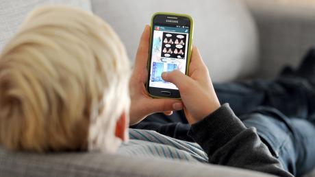 Zuhause alleine auf der Couch und doch mit allen Freunden in Kontakt: Das Handy macht's möglich.