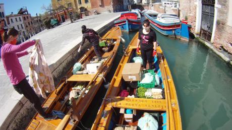 Drei Frauen mit ihren Vogas, traditionellen venezianischen Ruderbooten. Mit denen liefern sie Lebensmittel aus.