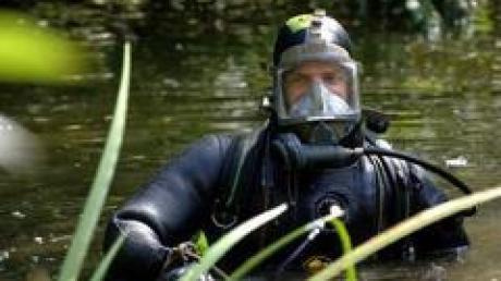 Ein Polizeitaucher untersucht in der Nähe eines Kieler Studentenwohnheimes, in dem ein mutmaßlichen Bombenleger gewohnt haben soll, einen kleinen Teich. Unter anderem wurde ein Computer im Wasser gefunden.
