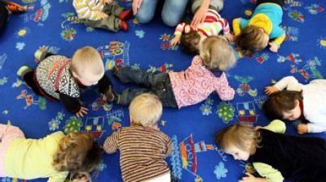 Kinder liegen in einer Kinderkrippe während eines Singspieles auf dem Boden. (Archivfoto)