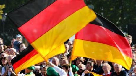 Eine Trachtengruppe präsentiert bei der Musikparade zum Tag der Deutschen Einheit die deutschen Farben.