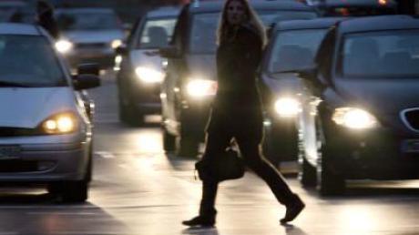 Eine Frau überquert vor wartenden Autos eine Straße in Düsseldorf. Für Berufspendler würde die SPD-Idee eine steuerliche Verbesserung bedeuten.
