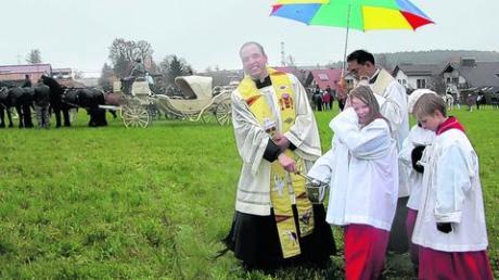 """Bei zuviel """"Segen von oben"""" braucht selbst die Geistlichkeit einen Regenschirm, wie hier beim Rundgang durch die Reihen der Tiere für den Leonhardisegen."""