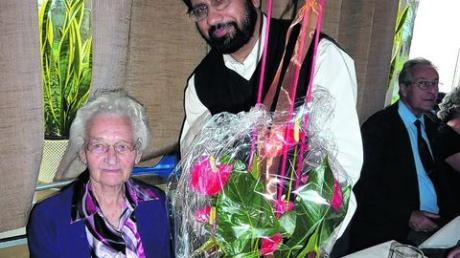 Mit einem Blumenstrauß ehrte Pater John die älteste Teilnehmerin des Seniorennachmittags bei der Kolpingsfamilie, Ida Wittmann. Foto: Janik