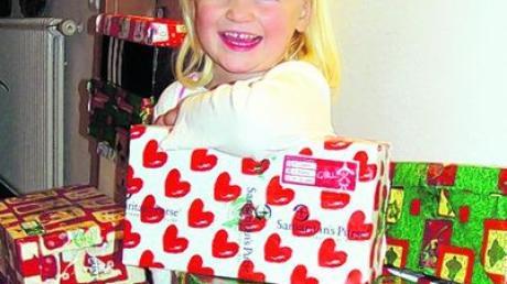 """Viele Päckchen gingen für die Aktion """"Weihnachten im Schuhkarton"""" ein. Im Bild Amelie Uhl zwischen ein paar der bunten Päckchen. Foto: Uhl"""