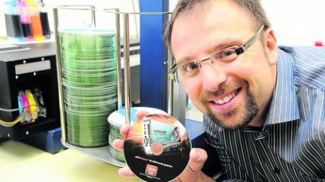 """Firmengründer Klaus Löffler zeigt eine der Polycarbonat-Speichermedien, die in seiner Werkshalle individuell bedruckt werden können. Er hat die Firma """"MK Discpress"""" vor 17 Jahren zusammen mit seinem Partner Wolfgang Kleinhappel aufgebaut."""