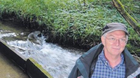 Pius Kirner, Fischwirt aus Unggenried, an einem Teilungswehr, an dem sich das Gewässer in Westernach und Brunnenbach teilt.