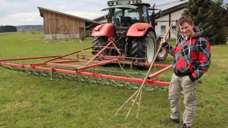 """Sechs Meter Arbeitsbreite gegen den deutlich eingeschränkteren, """"menschlichen"""" Radius: Markus Hemmerle aus Apfeltrach mit der Wiesenegge, die er sich mit zwei anderen Landwirten teilt, und der früher für die gleiche Arbeit genutzten Gabel."""