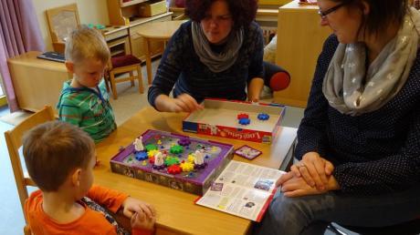 """Vincent (links) und Timo spielen mit ihren Müttern """"Logi-Geister"""". Wo muss man noch Zahnräder einfügen, damit sich alle Gespenster drehen?"""