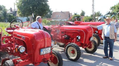 """Ins Auge stachen in Amberg gleich besonders drei knallrote, in den Jahren 1958 gebaute """"Porsche-Diesel-Traktoren"""" (Bild oben links) der Typen 133 (33 PS), """"Master"""" (50 PS) und """"Standart"""" (25 PS), die Reinhold Lösser aus Buchloe präsentierte. Da staunte auch ein vorbeifahrender Oldtimerfan mit Hund auf dem Beifahrersitz nicht schlecht. Ein Oldtimertreffen für die ganze Familie ebenso in Traunried (Bild unten rechts). Hier zog Siegfried Freisinger mit seinem Güllefass-Wohnanhänger (Bild obenrechts) viele Blicke auf sich."""