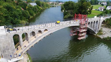 Die histroische Illerbrücke bei Lautrach wird derzeit saniert. Der linke Teil des Bogens (bis zum Hängegerüst) ist bereits fertig, rechts im Bild ist noch der alte Zustand zu sehen. Im Hintergrund sieht man die Illerbrücke, die der Landkreis im Jahr 2010 neu gebaut hat.