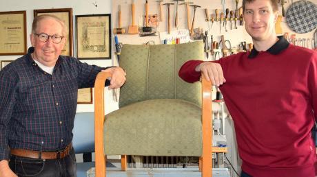 """Hier übergibt Michael Probst (links) den selbstgepolsterten """"Chef-Sessel"""" an seinen Sohn Wolfgang, der nun den Raumausstatter-Handwerksbetrieb in der fünften Generation in Folge übernommen hat."""