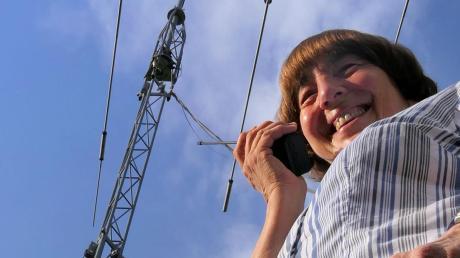 """Unser Bild zeigt Gertrud Reschke im Garten mit ihrer """"Doppel-Antenne"""" Fritzel-Beam FB-Do 450 und Magnetic Loop AMA 10D. Nicht zu sehen sind ihre Langdraht-Antenne und ein Rundstrahler auf dem Hausdach. In der Hand hält sie eines ihrer kleineren Funkgeräte. Sie hat aber noch ein großes Gerät, einen Kenwood HP Transceiver für Kurzwelle."""