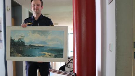 Kommissar Stefan Wahmhoff von der Polizei in Bad Wörishofen mit den Gemälden, die nahe der Autobahn A 96 bei Wiedergeltingen von einer 62-jährigen Frau gefunden wurden.