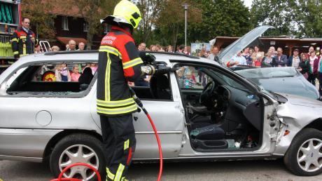Unter den wachsamen Augen des Vorsitzenden Robert Kugelmann (li.) zerschneidet der Ettringer Feuerwehrkamerad mittels Rettungsspreizer das Fahrzeug. Das Publikum nimmt gebannt Anteil.