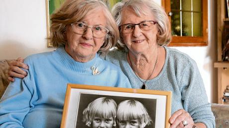 Anna Holzheu (links) und Gertraud Abröll sind eineiige Zwillinge und leben seit 20 Jahren gemeinsam im selben Haus. Aus ihrem Heimatort Erkheim sind sie nicht wegzudenken. Die Unterallgäuerinnen halten ein Foto in Händen, auf dem die beiden als Kinder zu sehen sind.