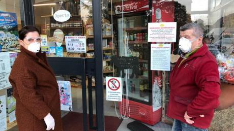Mit Atemschutz-Masken für Maler geht Maria-Grazia Tosi zusammen mit ihrem Ehemann Tiziano in Verbania einkaufen.