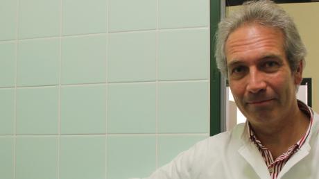 Virologe Dr. Matthias Lapatschek mit dem Gerät, mit dem Viren nachgewiesen werden können.