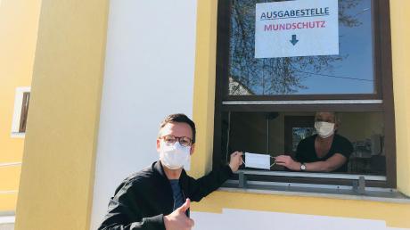 Bürgermeister Peter Wachler und die Verwaltungsangestellte Manuela Pfluger zeigen, wie die Ausgabe der Masken am Rathaus funktioniert.