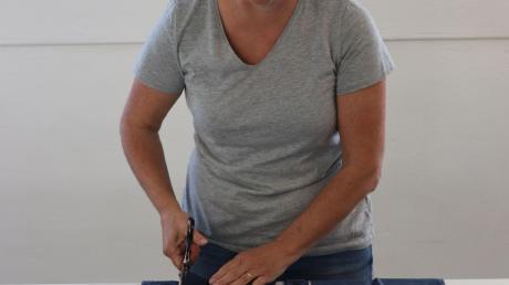 Andrea Haslacher schneidet aus einem gespendeten Hemd Stoff für Mund-Nasen-Masken.