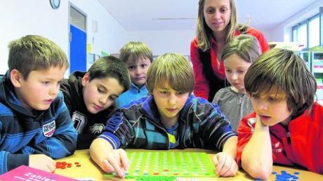 Mit dem richtigen Spiel macht selbst Mathe Spaß. Das finden (unten v. li.): Raphael (10), José (7), Maximilian (7), Sebastian (12), Pia (6), Christian (12) sowie die Leiterin der Ganztagsbetreuung in Pfaffenhausen, Martina Dietmayer. Foto: home