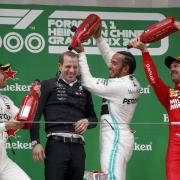 Sebastian Vettel (r) spendiert für Sieger Lewis Hamilton eine Champagner-Dusche. Foto: Andy Wong/AP