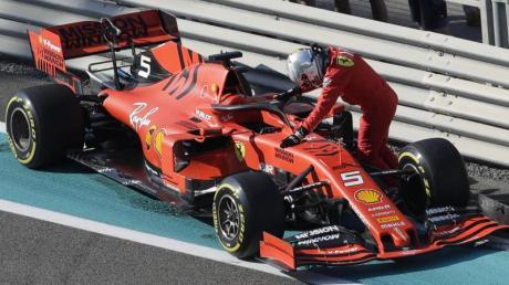 Braucht dringend ein neues Dienstfahrzeug: Sebastian Vettel stützt sich auf seinen liegengebliebenen Rennwagen.
