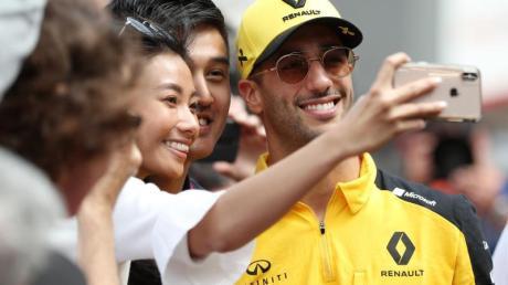 Der Australier Rennfahrer Daniel Ricciardo lässt sich von Fans fotografieren.
