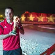 Goldjunge: Lukas Podolski mit dem WM-Pokal 2014. Foto: Ges/Markus Gilliar