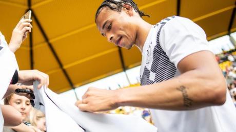 Nach einer öffentlichen Trainingseinheit gibt Leroy Sané in Aachen Autogramme.