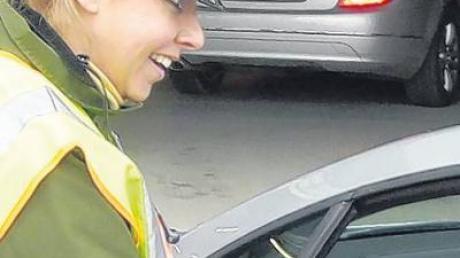 Eine Polizeibeamtin beim Verteilen von Flugblättern.