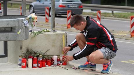 Razvan Iuga zündet eine Kerze an der Stelle an, an der sein bester Freund in der Nacht auf Donnerstag bei einem tragischen Motorradunfall ums Leben gekommen ist.