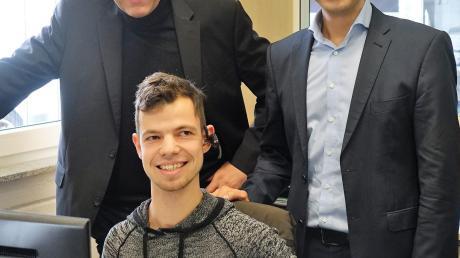 Patrick Juchum (sitzend) mit Geschäftsführer Dietmar Renz (links) und mit Mathias Auch von der Agentur für Arbeit Ulm.