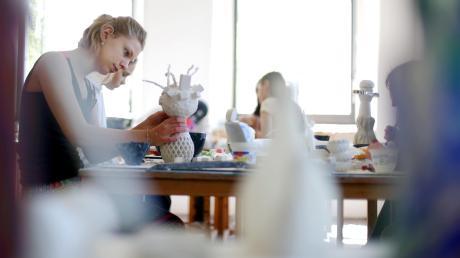 Bei der Ferienakademie im Kloster Roggenburg dreht sich alles um Kunst: Die 16-jährige Carlotta (oben) arbeitet an einer Skulptur aus Gips, während die 14-jährige Annalena (unten links, graues Shirt) Hip-Hop tanzt.
