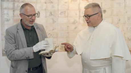 Matthias Kunze, Leiter des Weißenhorner Heimatmuseums, und Pater Roman Löschinger, Leiter des Bildungszentrum, sind begeistert von Kuens Werken. Die Ausstellung ist bis 1. Dezember in Roggenburg zu sehen.