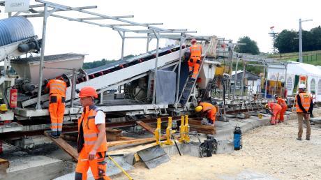 Bei den Arbeiten geht es Schritt für Schritt weiter in Richtung Stuttgart – jeden Tag wollen die Arbeiter etwa 200 Meter Schienen verlegen. Die weißen Zelte schützen den Beton der Festen Fahrbahn vor Witterungseinflüssen.